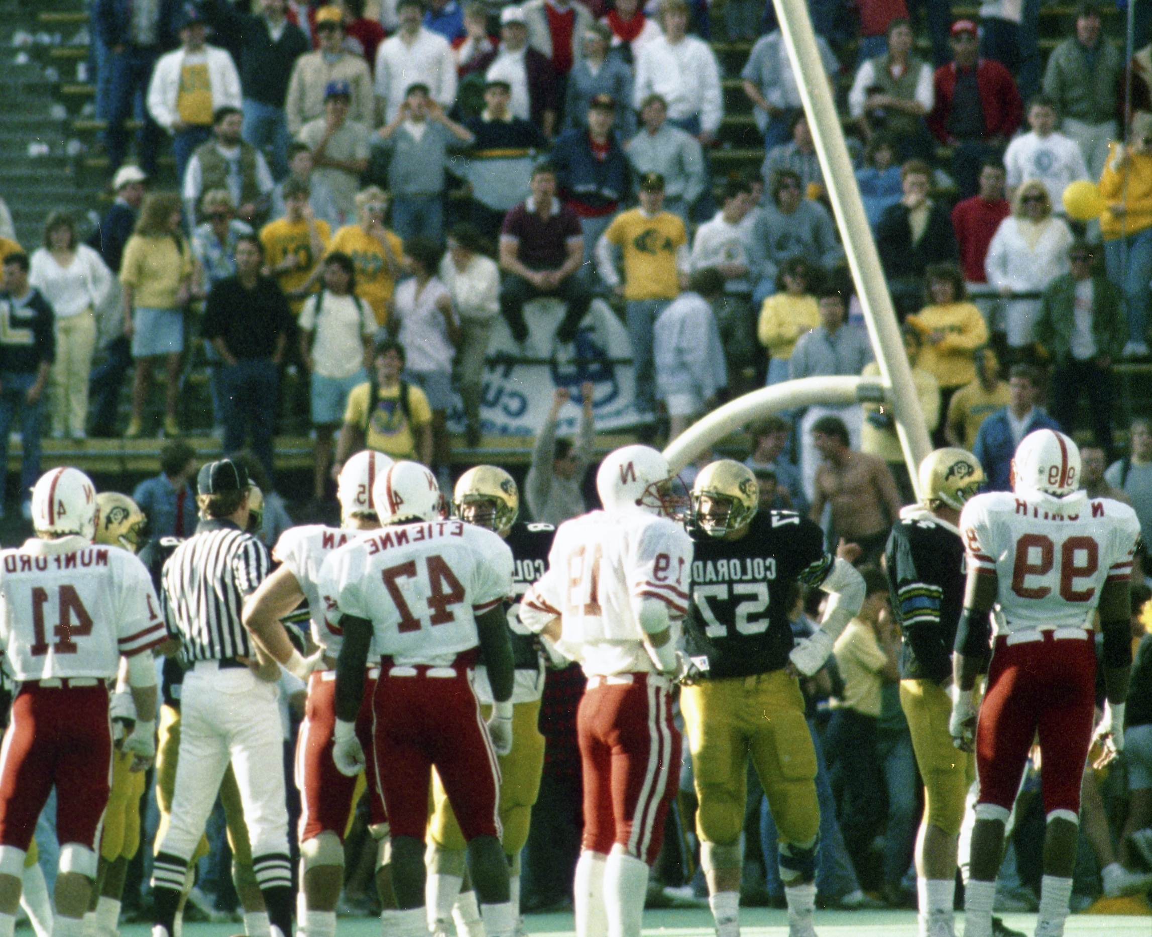 An archive photo from the 1986 CU vs. Nebraska game where fans rushed the field, toppling over a goal post.