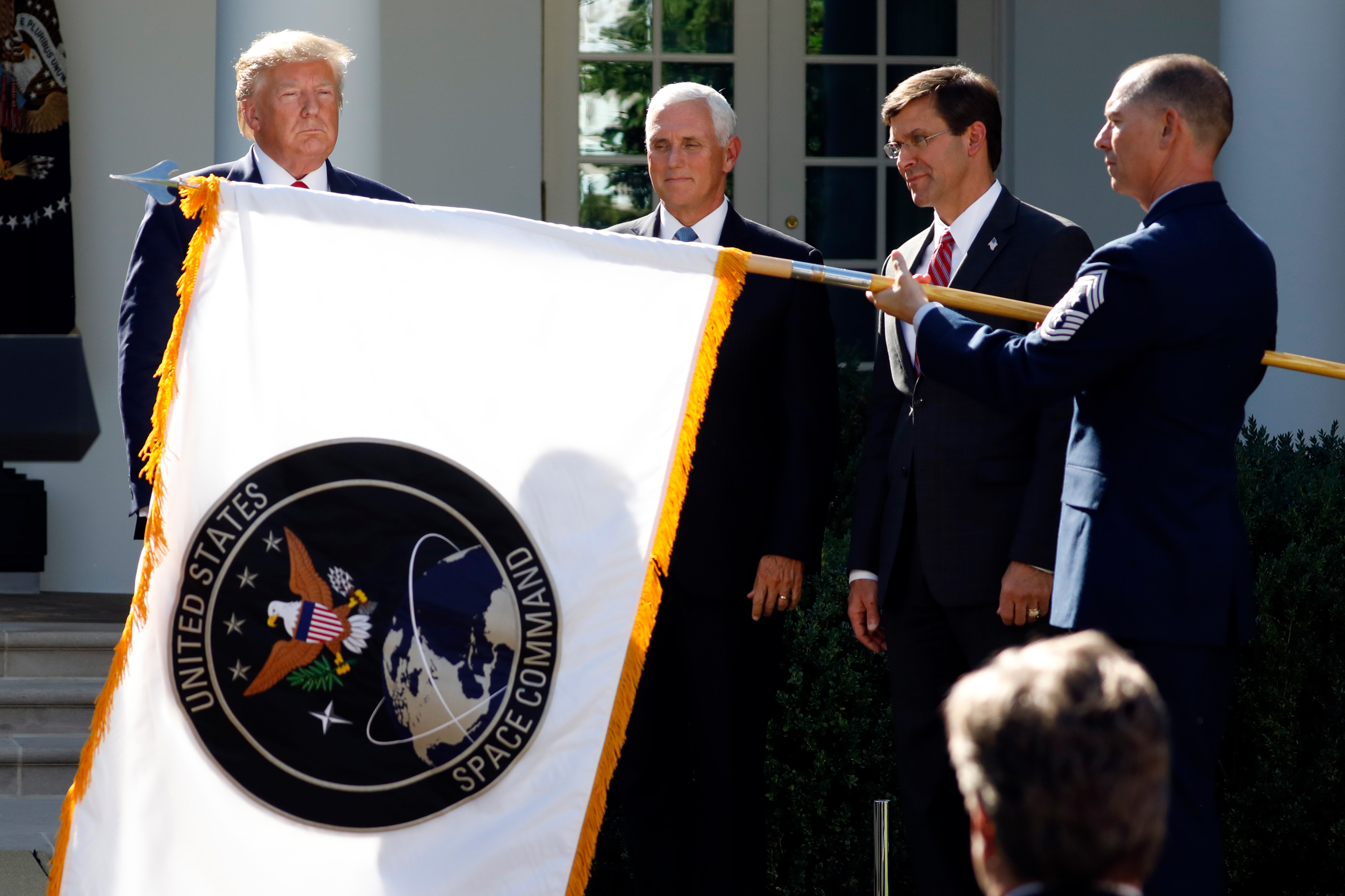 President Donald Trump watches with Vice President Mike Pence and Defense Secretary Mark Esper as the flag for U.S. space Command is unfurled as Trump announces the establishment of the U.S. Space Command in the Rose Garden of the White House in Washington, Thursday, Aug. 29, 2019.