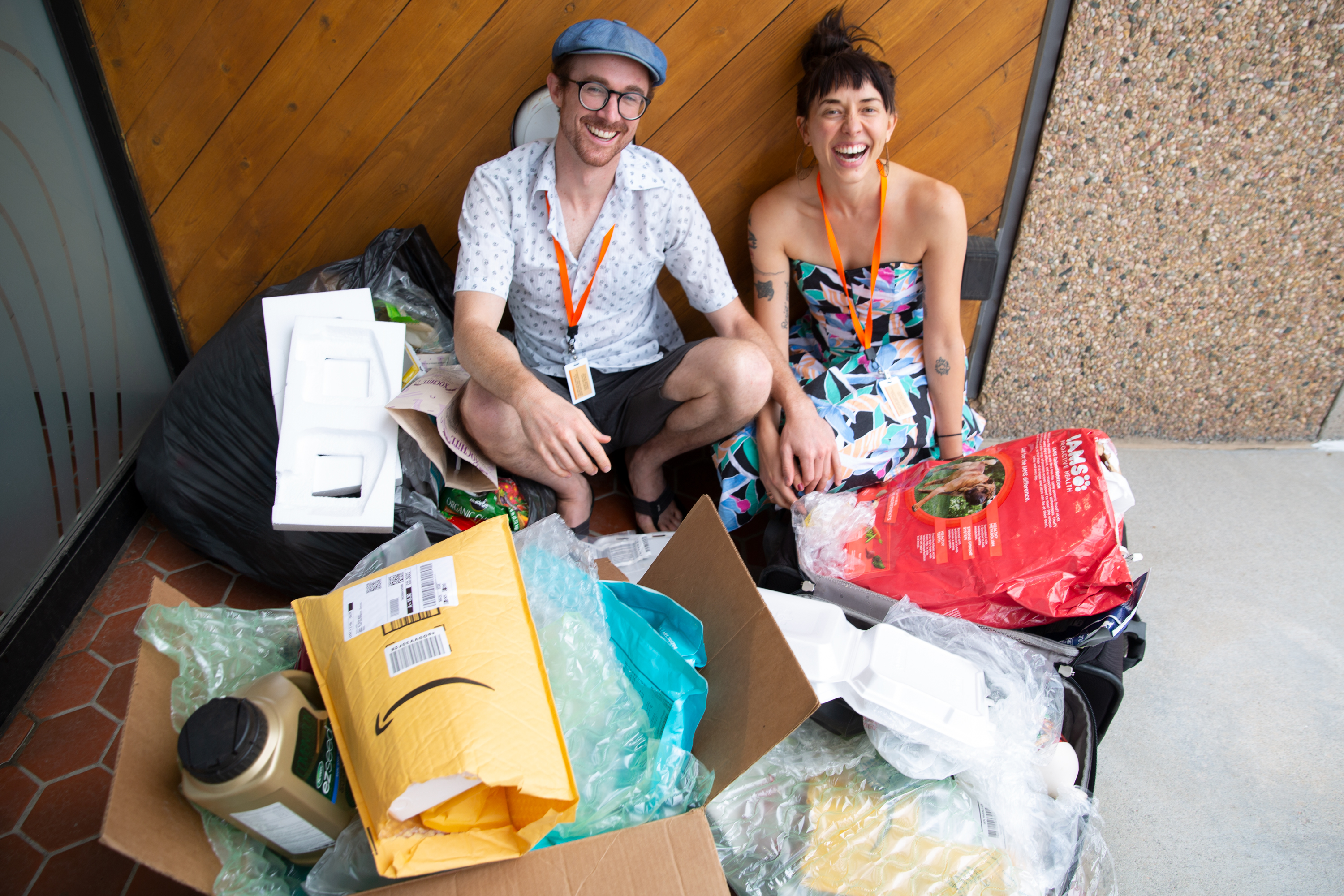 "Kevin Larkin and Erica Prather sit amongst all the plastic they've used so far in 2019. It's contained in one suitcase, a large box and a large trash bag — their ""Pile of Petroleum Past."""