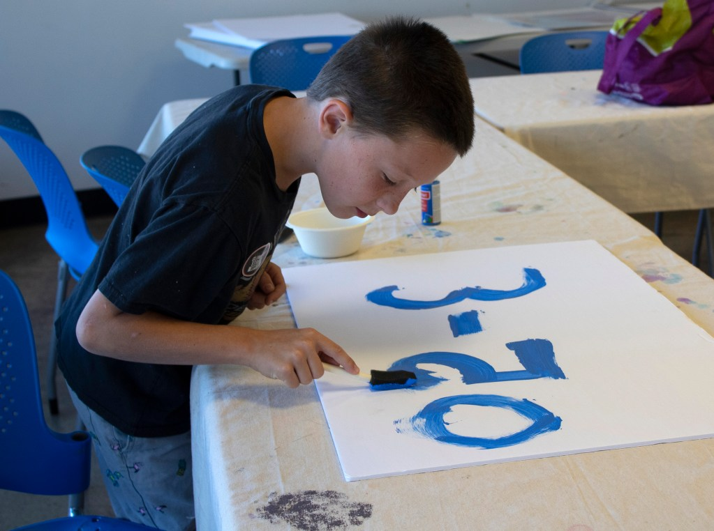 9-year-old Dylan Gray painting a sign for the Colorado Springs youth climate strike