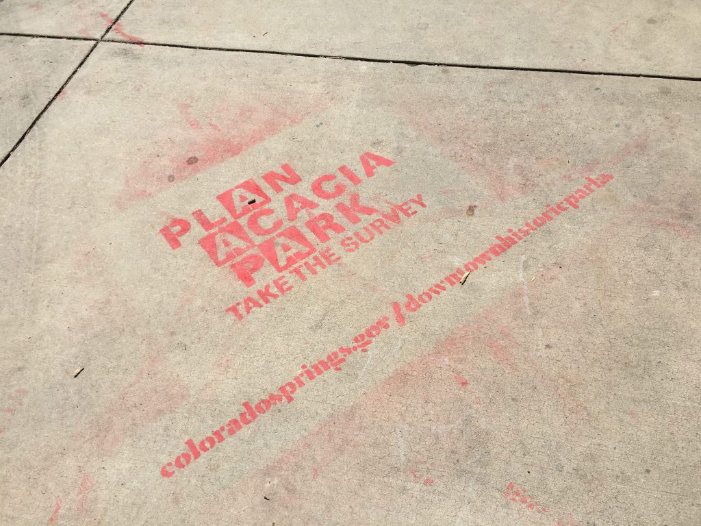 Sidewalk art calling for residents to participate in the city's survey about three historic downtown parks.