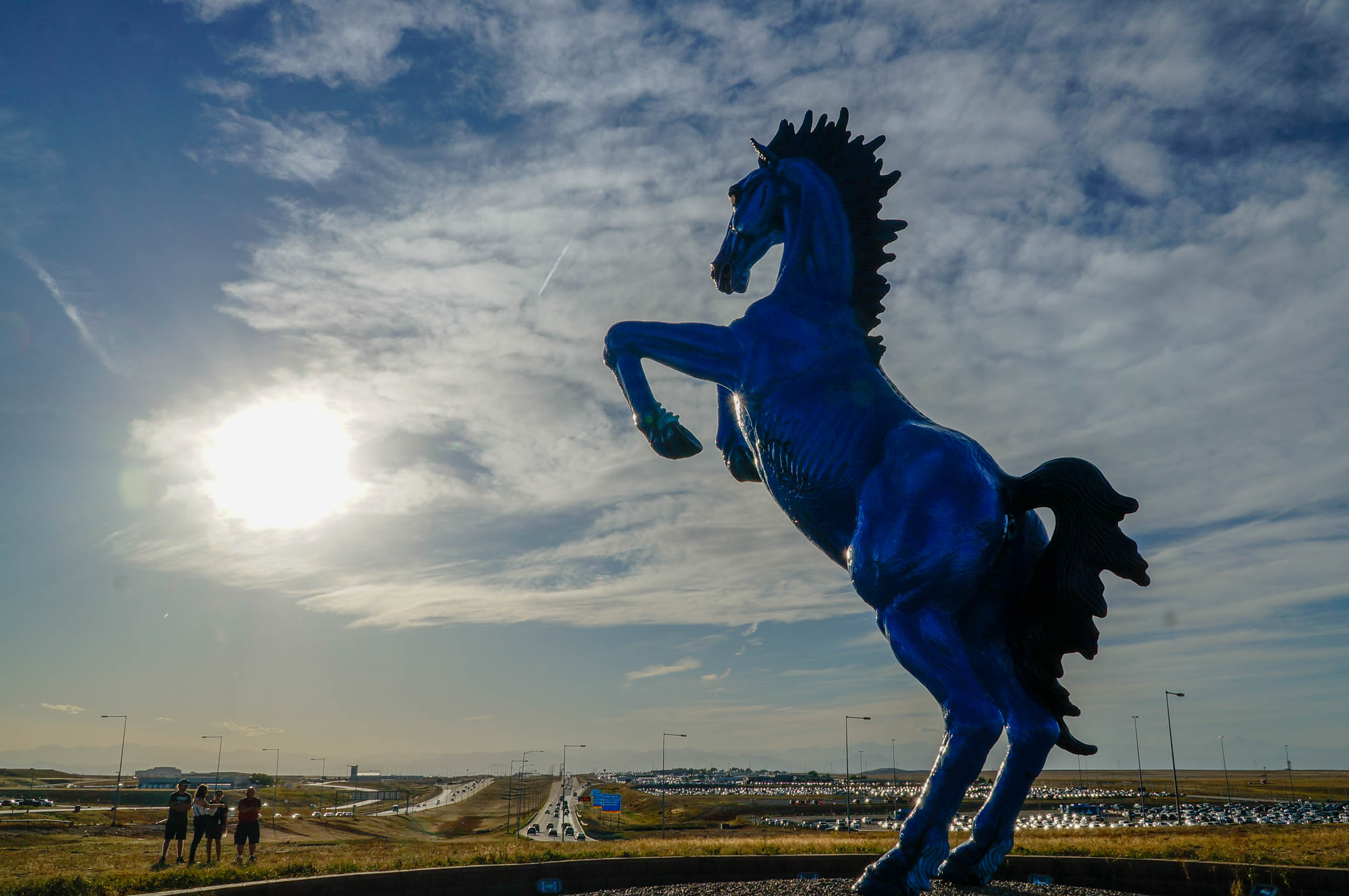 "The 32-foot-tall fiberglass ""Mustang"" towers over Colleen Donohue, Alex Renteria, Adam Horst and Michael Gunstanson at the Denver International Airport on Sept. 25, 2019."