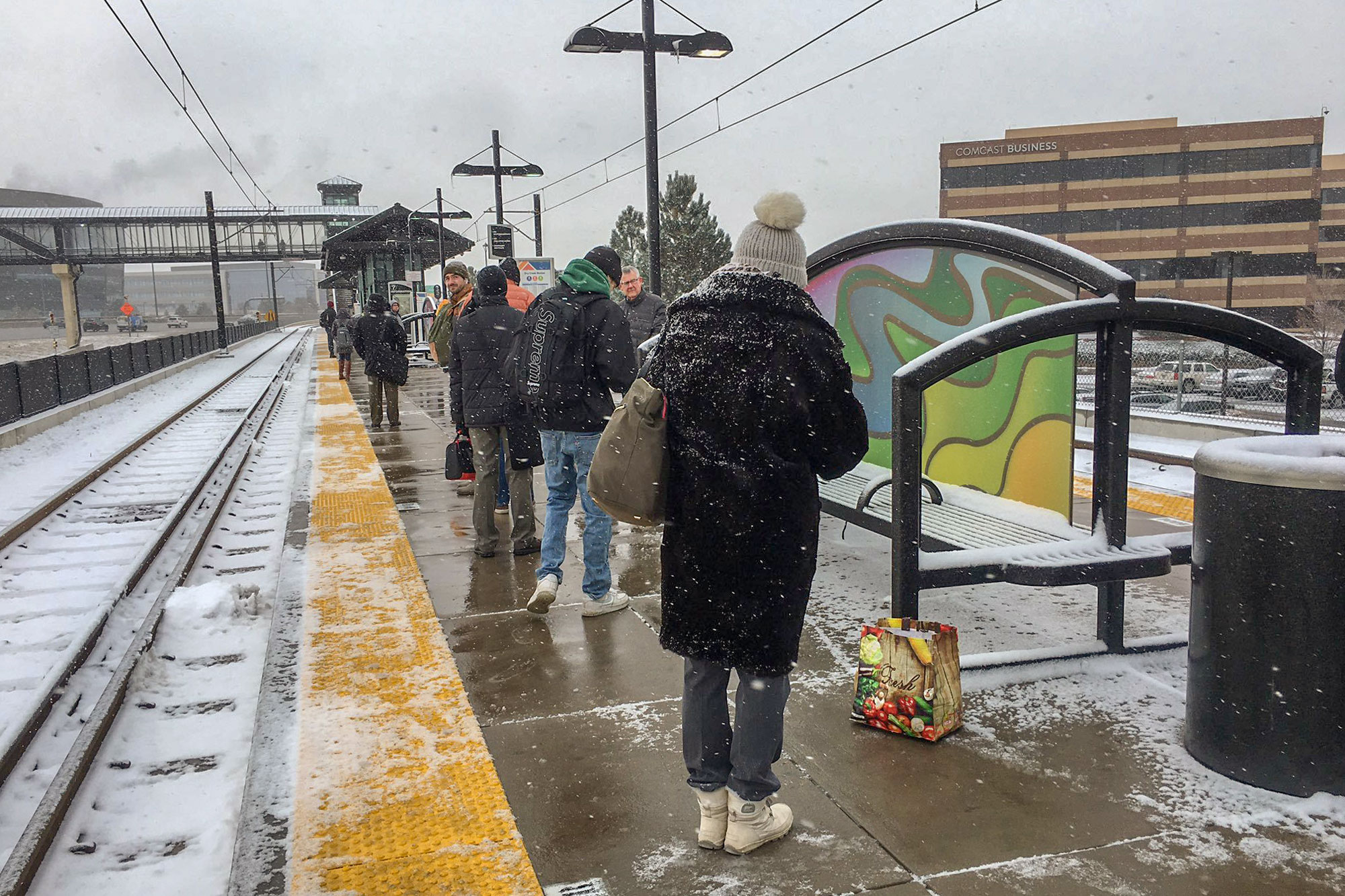 Commuters huddle agains the elements as they wait for a northbound train at the Dry Creek Station in Centennial, Colo., Nov. 11, 2019.