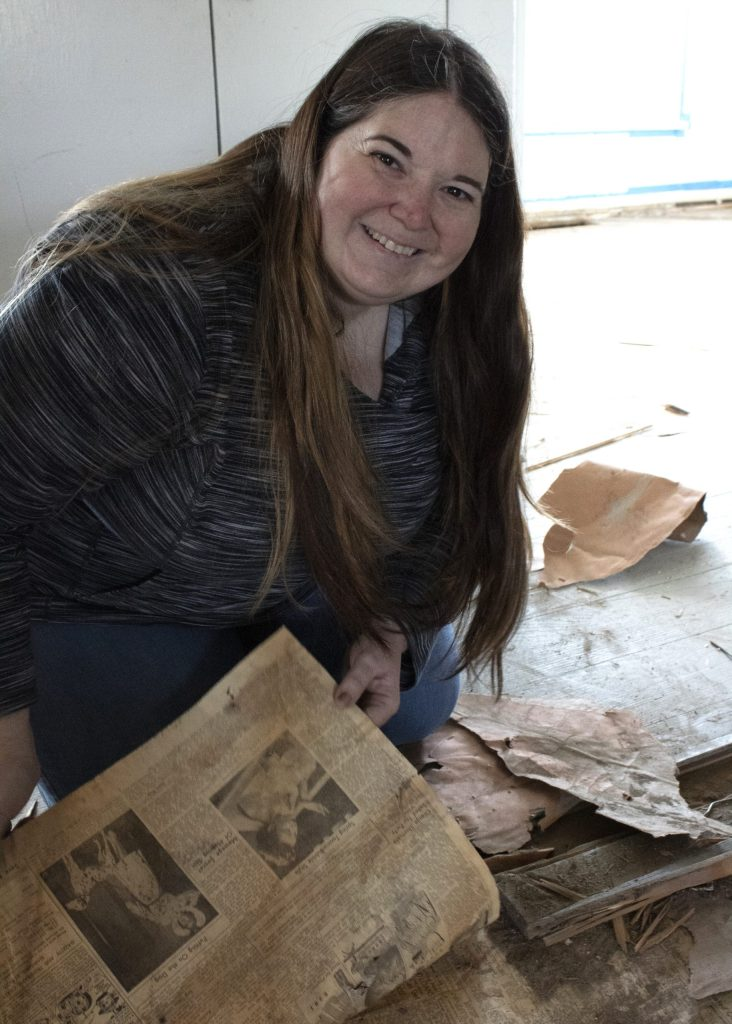 Genesis De Leon lifts up a page of newspaper found under the floor in her home.