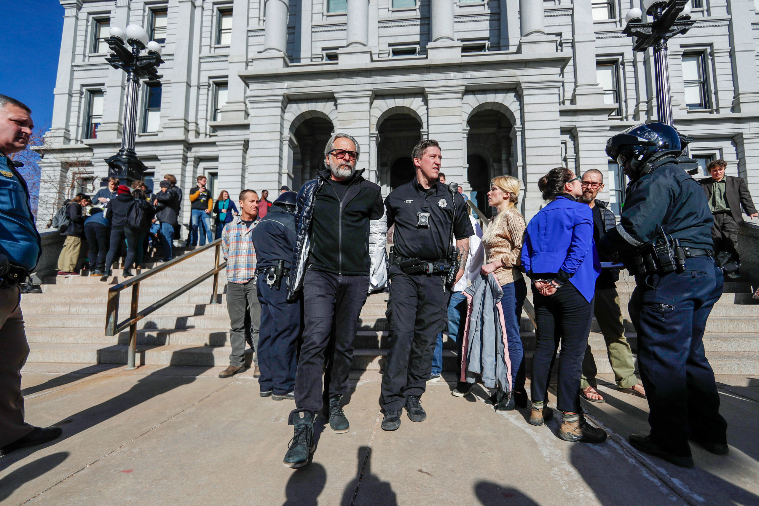 A Denver Police Department officer leads away one of several anti-fracking protesters who interrupted the State of State speech by Colorado Gov. Jared Polis, Jan. 9, 2020, in Denver.
