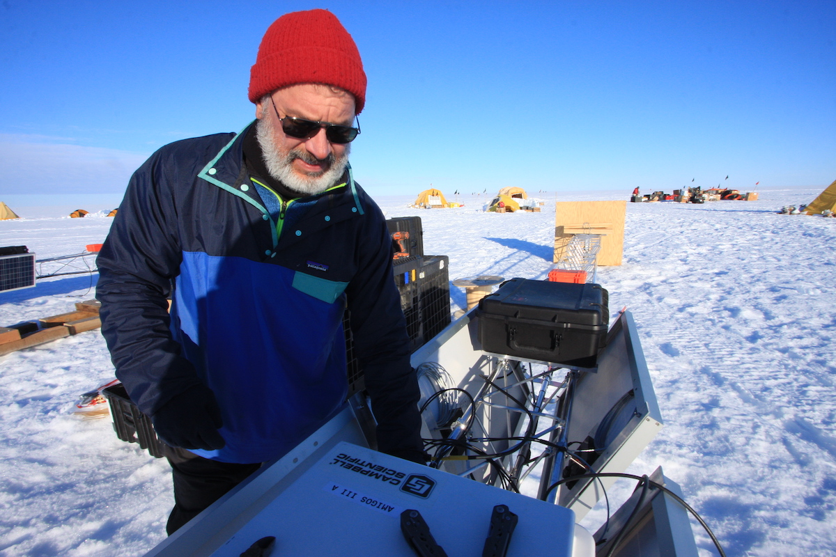 Glaciologist Ted Scambos with equipment he's installing at Thwaites Glacier to measure weather and sea conditions.