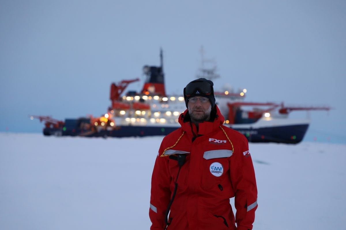 University of Colorado scientist Matthew Shupe in 2019 stands in front of Polarstern during the MOSAiC mission. The ship is moored to an ice floe drifting through the Arctic Ocean.
