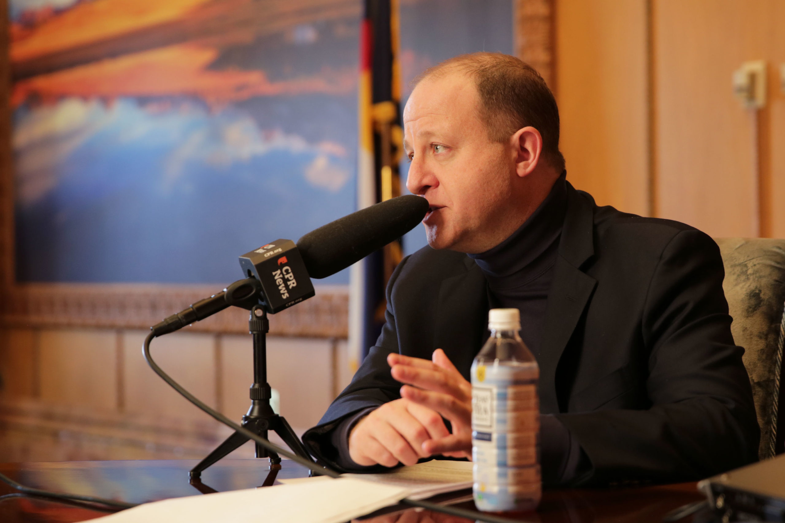 Gov. Jared Polis talks with Colorado Matters host Ryan Warner in his office at the state Capitol on Feb. 27, 2020.