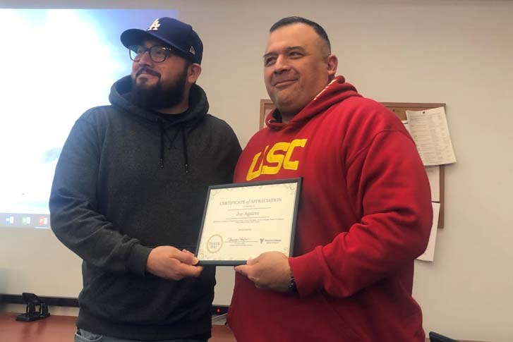 Robert Hernandez (left) poses with Joe Augirre, as Augirre holds an award for fixing another veteran's mobile home.
