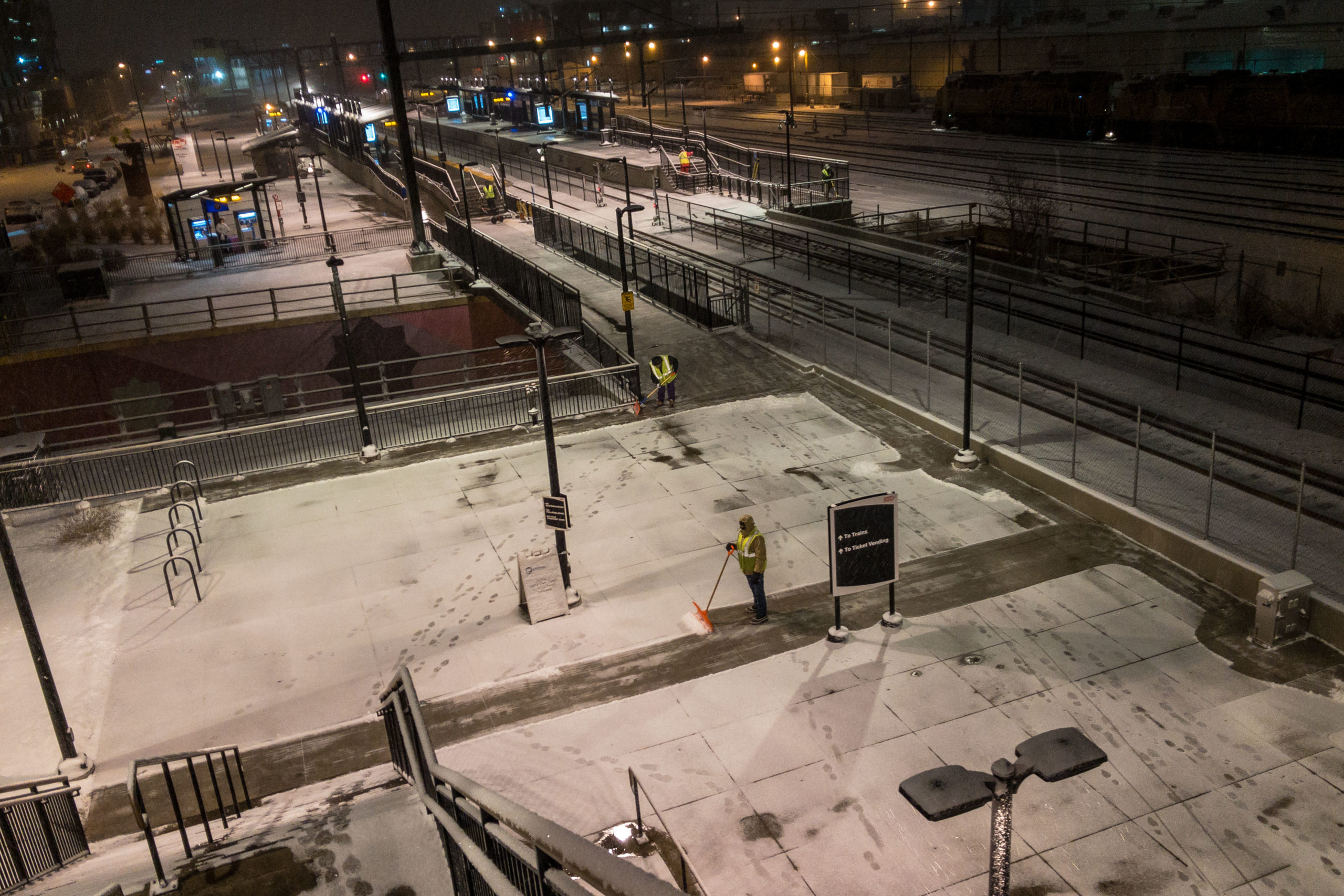 Shovel crews works to clear the snow at the RTD 38th and Blake commuter rail station ahead of rush hour, Feb. 4, 2020.