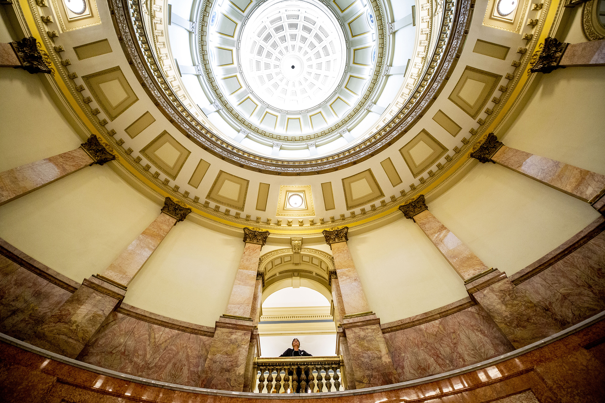 A woman peers into the Colorado State Captiol rotunda. March 12, 2020. (Kevin J. Beaty/Denverite)