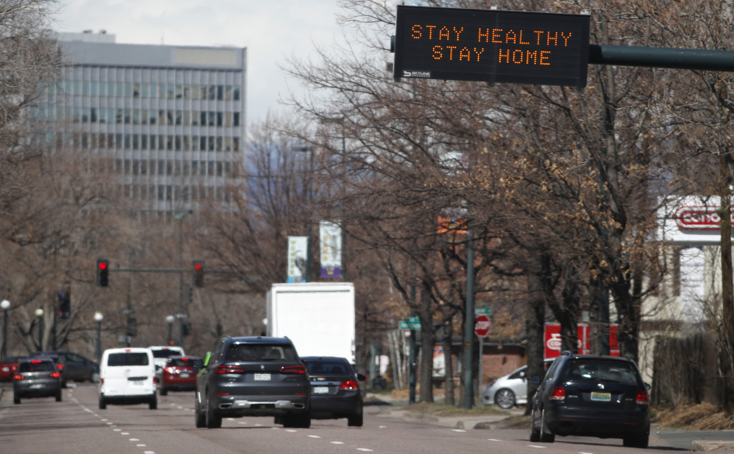 "A traffic sign over westbound Speer Boulevard tells motorists to stay home as a mayoral ""stay at home"" edict goes into effect until Friday, April 10, in an effort to reduce the spread of the new coronavirus Tuesday, March 24, 2020, in Denver."