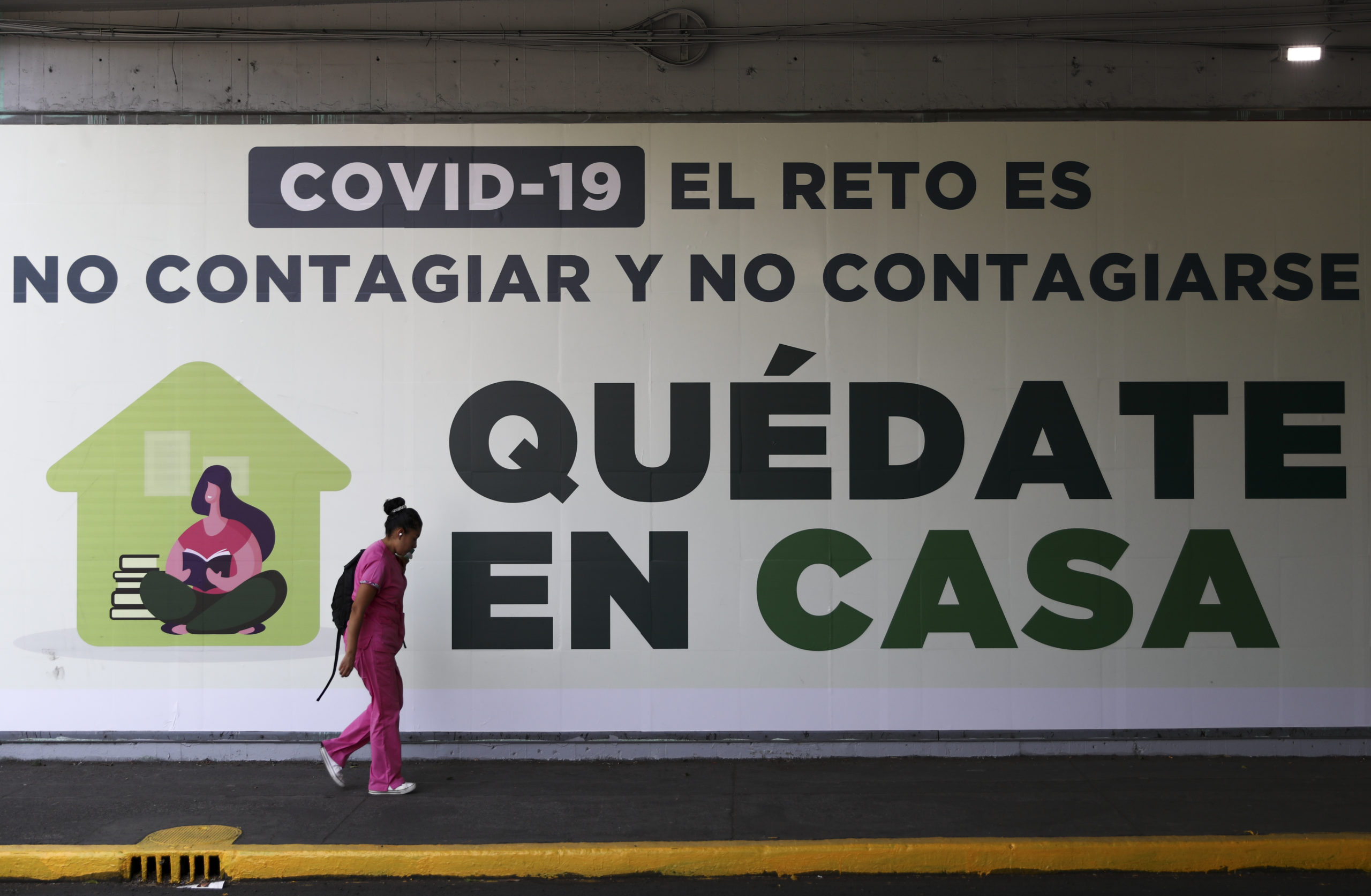 "A woman walks past a sign that reads in Spanish ""COVID-19. The challenge is not to get it and not spread it. Stay home,"" in Mexico City, March 31, 2020."