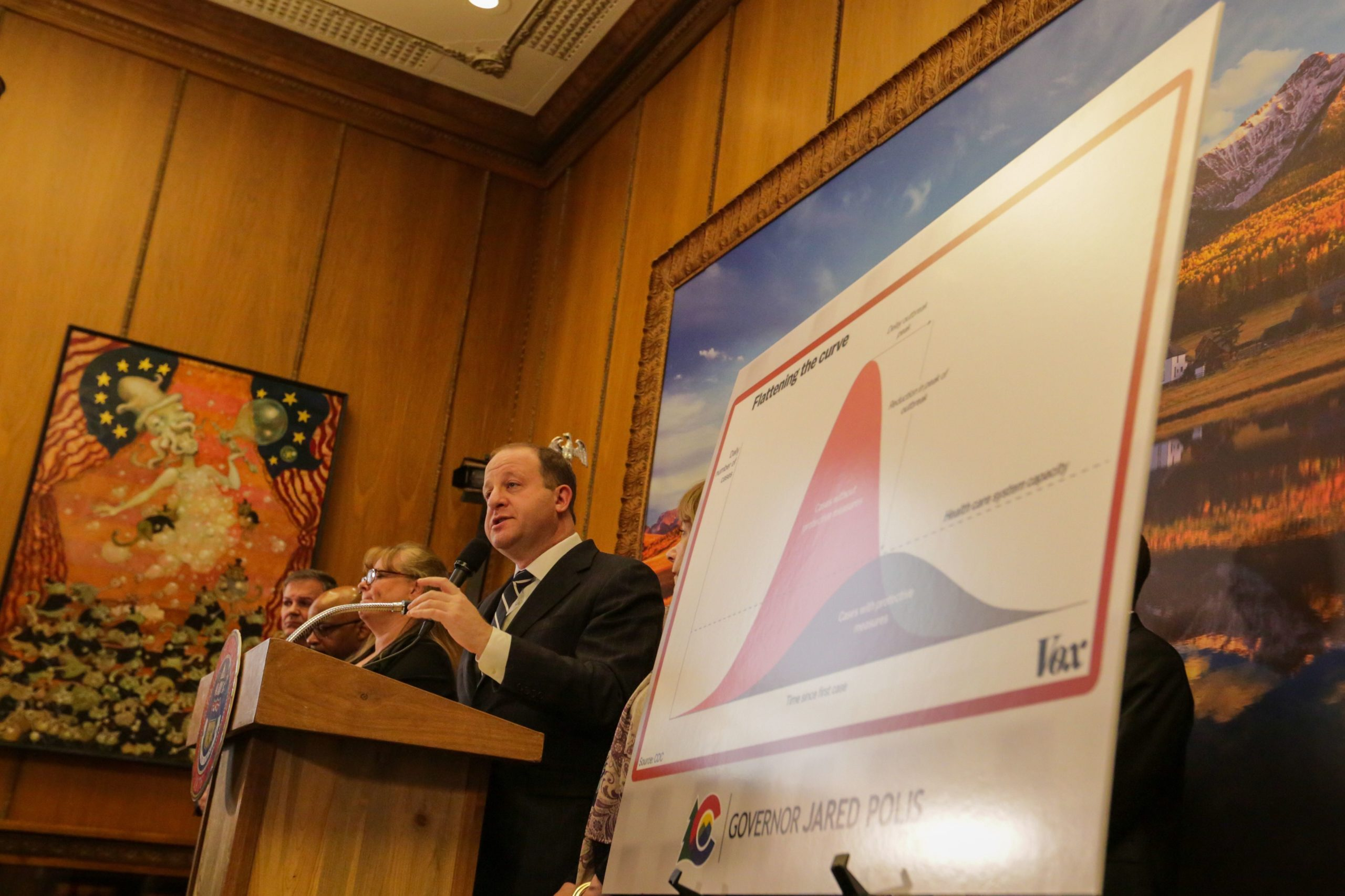 "Gov. Jared Polis provides an update on coronavirus in Colorado on Friday, March 13. Next to him is a version of the popular ""flatten the curve"" chart about slowing the spread of an epidemic."