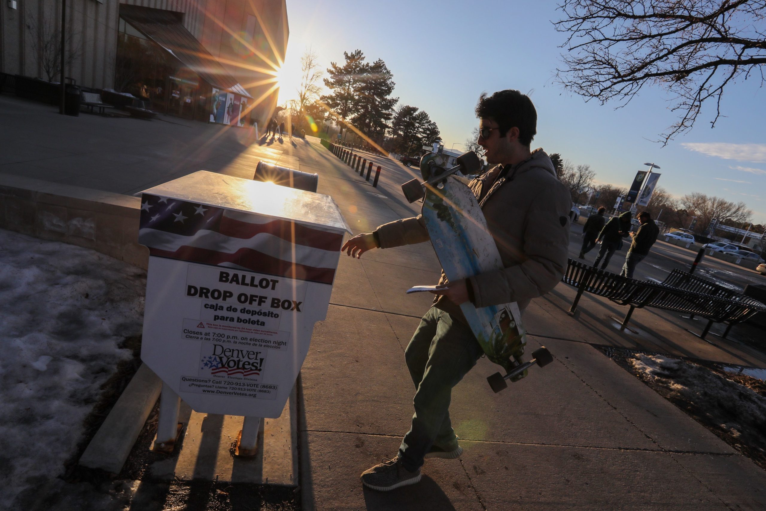 A late-day voter cradles his skateboard as he drops off his ballot at the Denver Museum of Nature and Science.