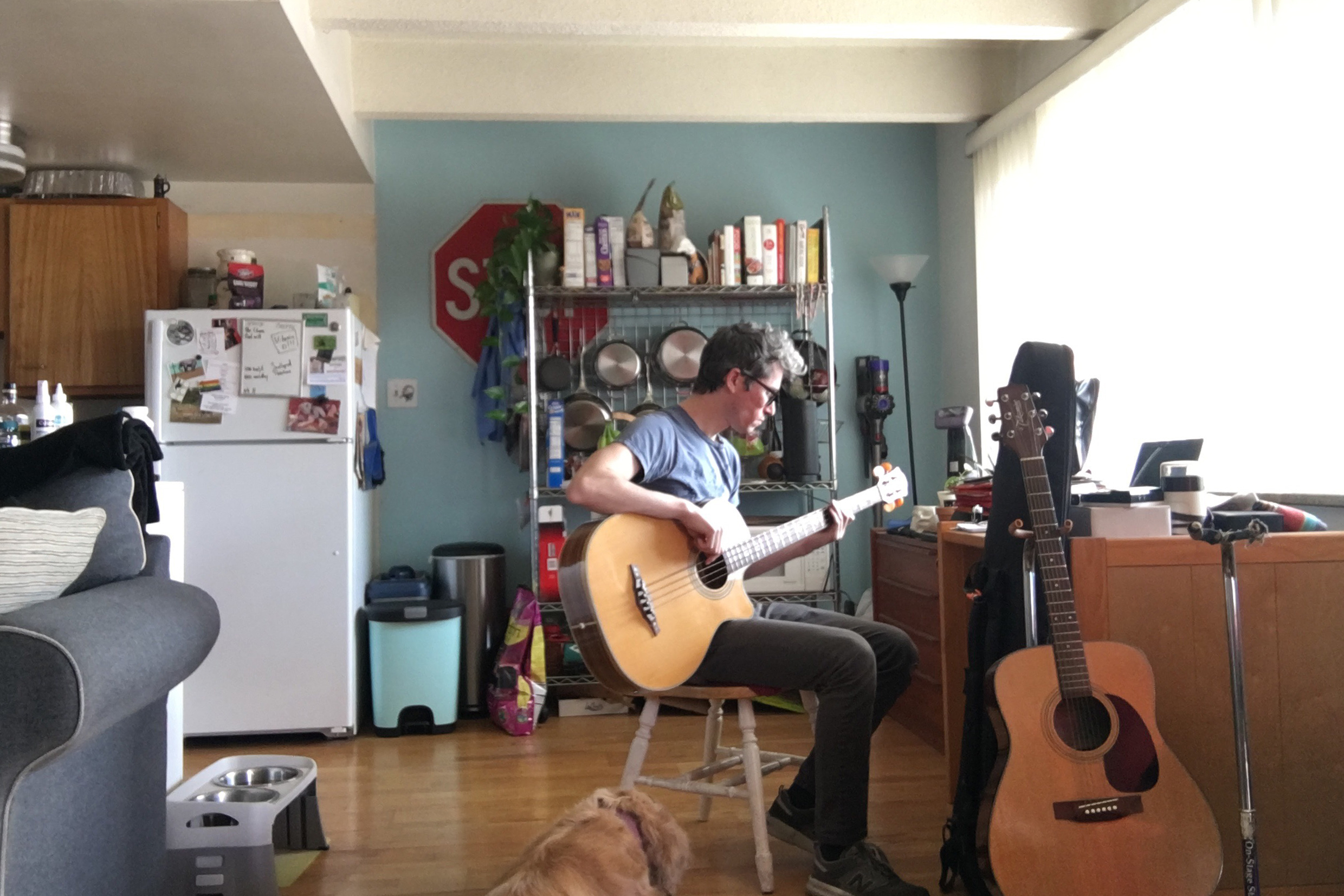 Michael King plays his guitar at his home after getting his hours cut from his job as a baker, March 31, 2020.