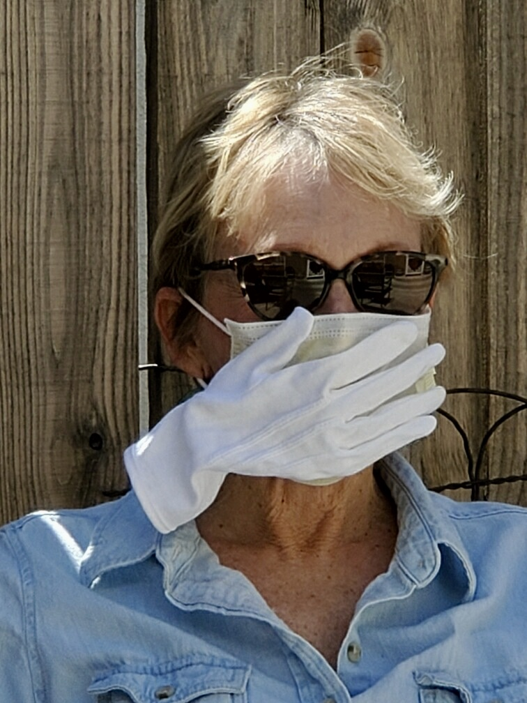 A picture of Cathleen in front of a wooden fence wearing a face mask and sunglasses.