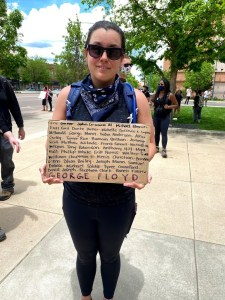 Jessica Cheathum stands with her sign indicating names of people killed.