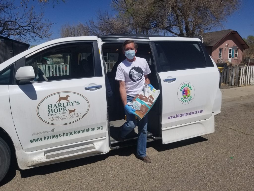 A picture of David, wearing a white shirt, mask and gloves, stepping out of the sliding door of a white van with the Harley's Hope Foundation logo.