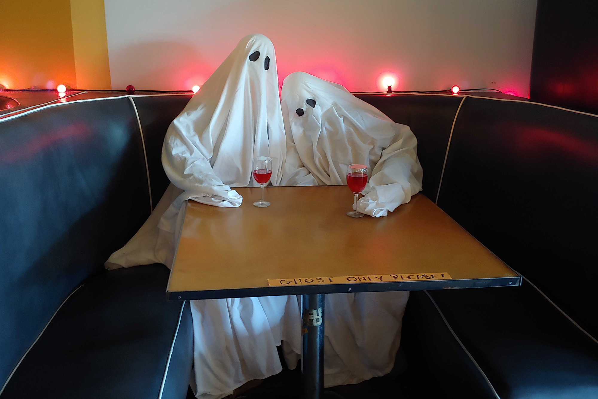 Two lovebird ghosts snuggle up at a booth in the Denver restaurant Sputnik.