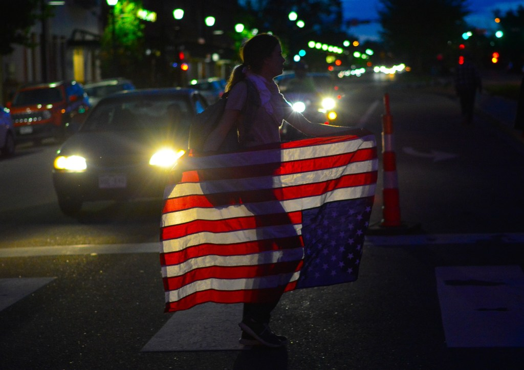 "Christine Smith of Castle Rock, CO carries an upside down American flag while crossing Nevada Ave. in downtown Colorado Springs on June 2, 2020. ""These people are in distress,"" she said as she joined hundreds of other demonstrators."
