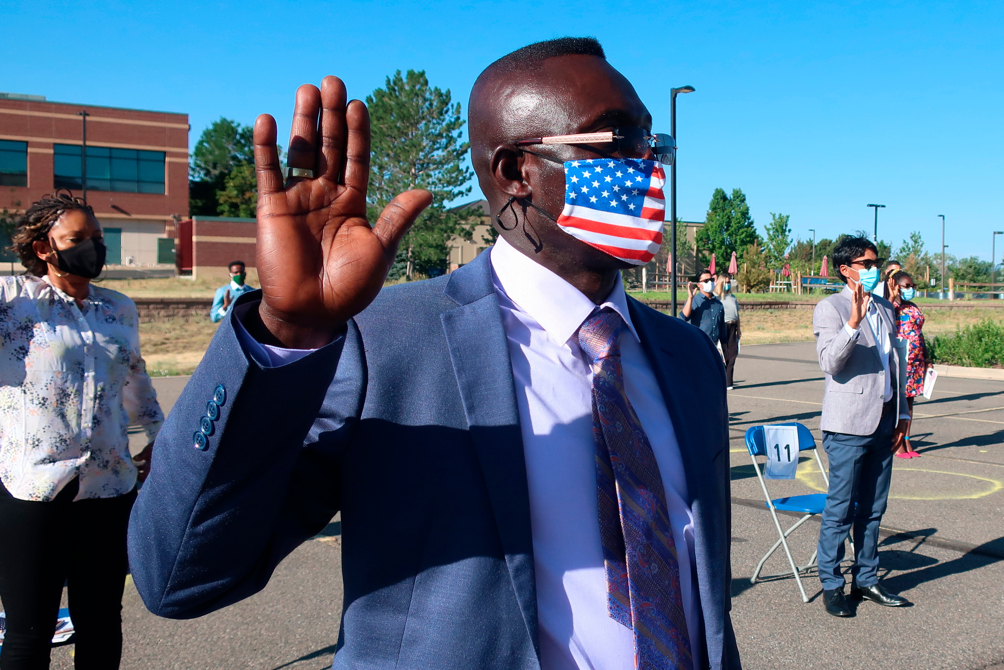 Candidate for naturalization Jeremy Owusu takes his oath to become a U.S. citizen in front of the Denver USCIS field office on Friday, July 17, 2020. He and 33 others became citizens in a ceremony unique to the COVID-19 pandemic.