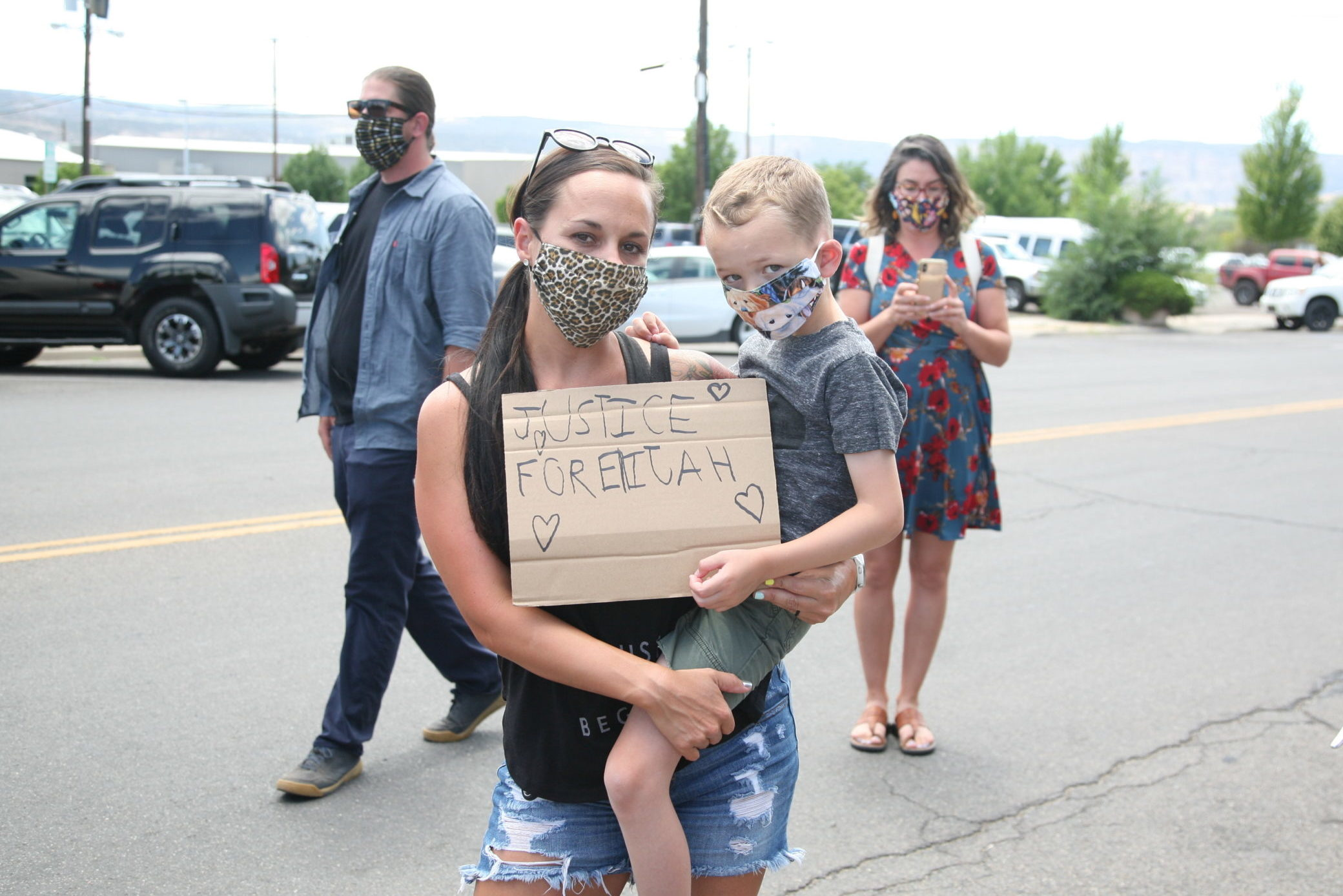 A demonstrator shows off her sign outside of Gov. Jared Polis' bill signing event in Grand Junction, July 6, 2020.