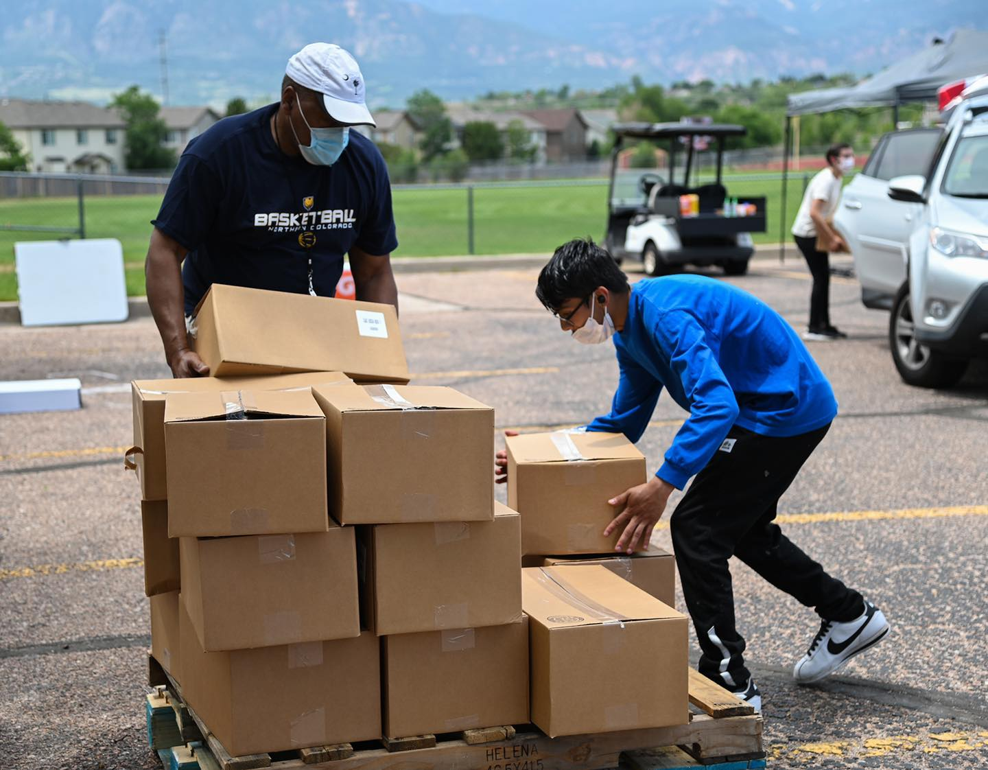 A photo of two volunteers for Care and Share loading boxes of food.