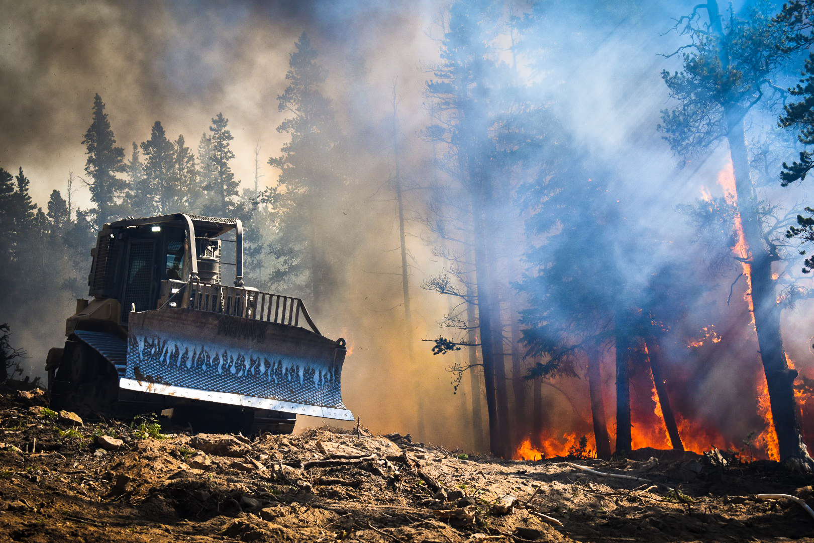 A bulldozer drives along a perimeter near the Cameron Peak Fire west of Fort Collins.