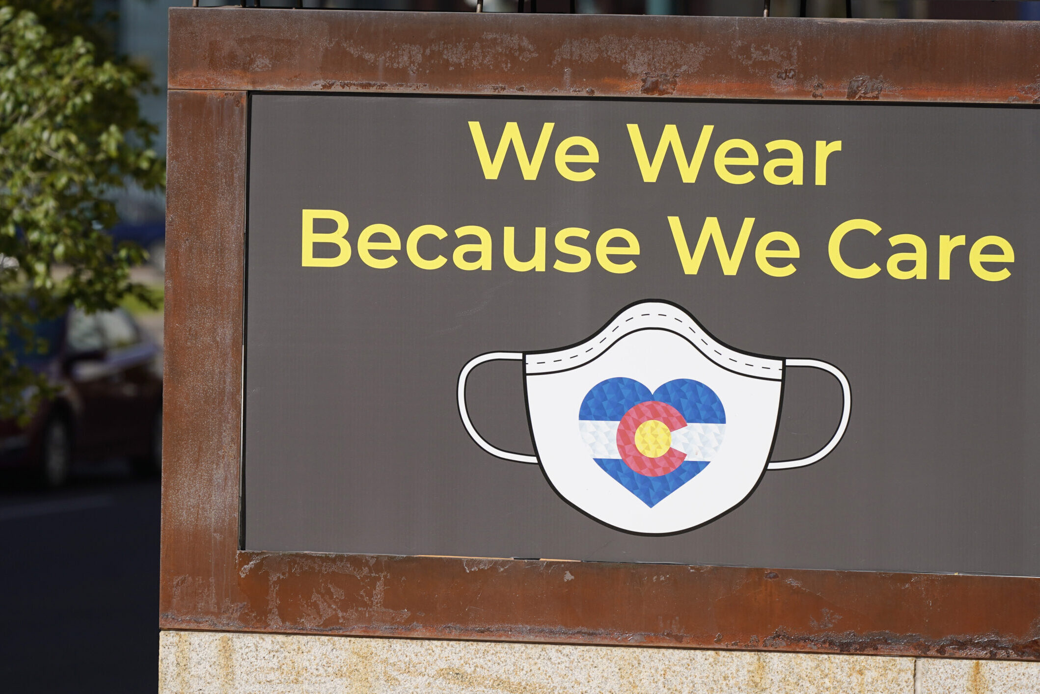 A sign in Denver encourages face masks.