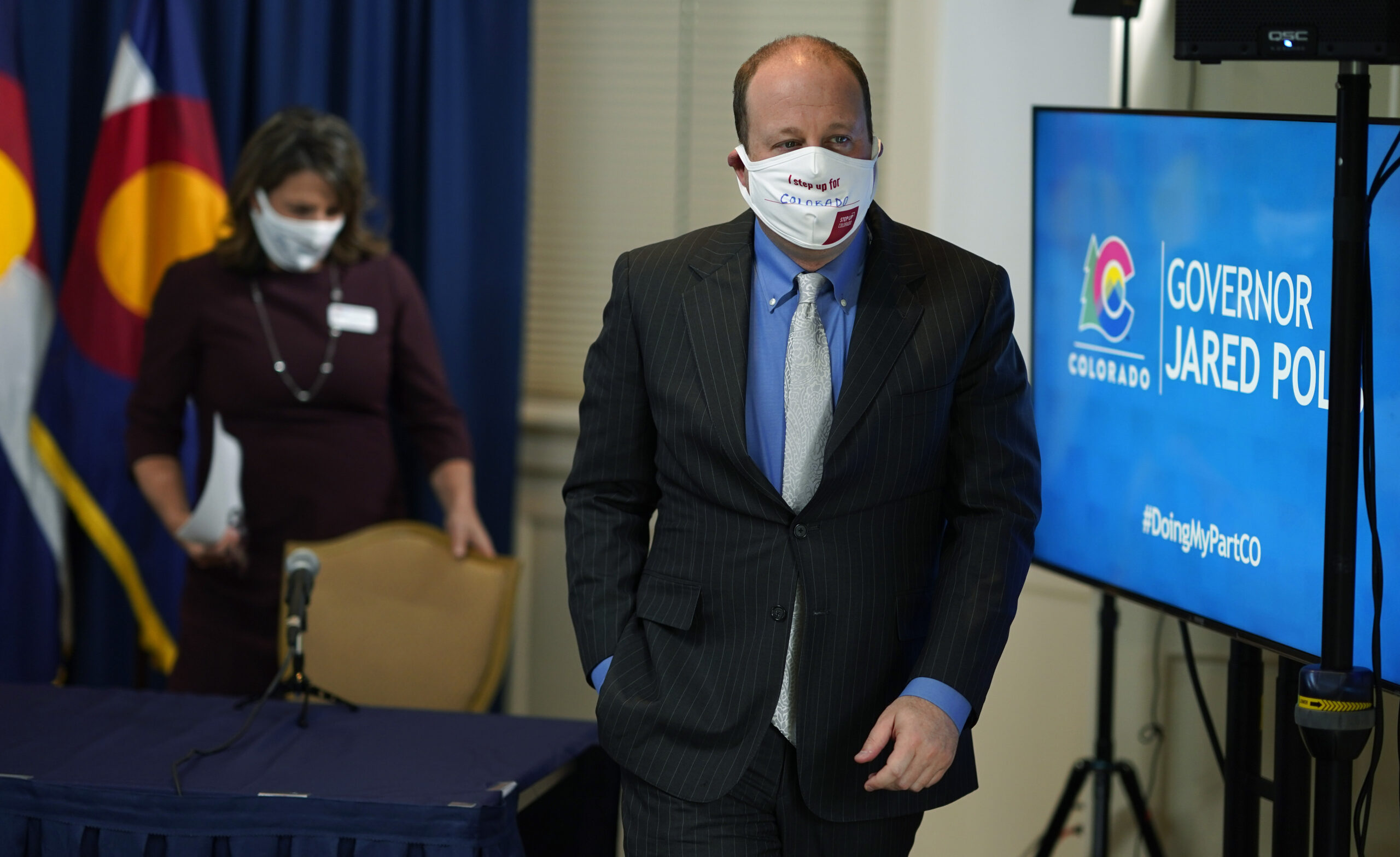 Jared Polis, front, and Jill Ryan, executive director of the Colorado Department of Public Health and Environment, leave after a news conference.