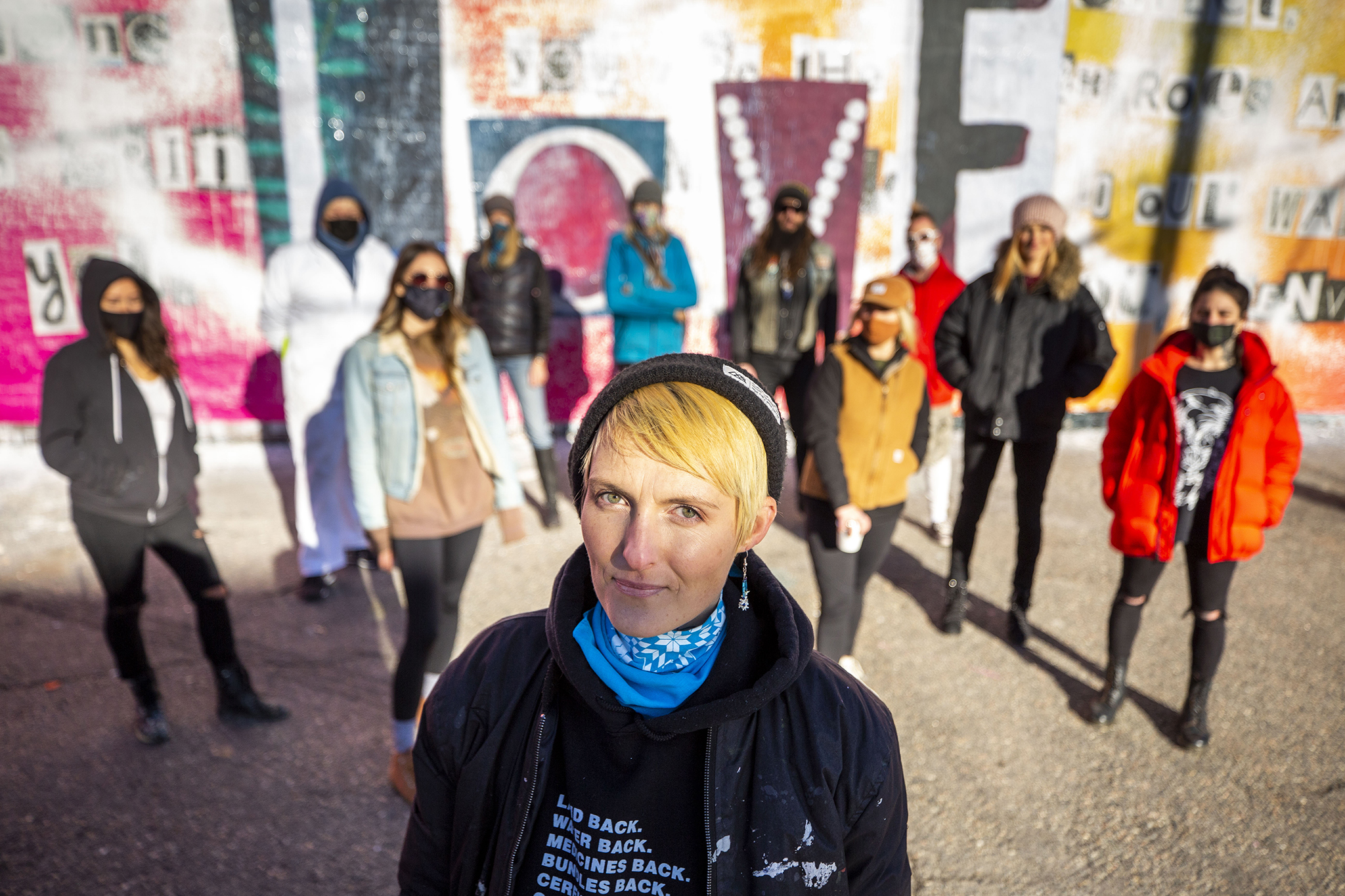Surrounded by friends and supporters, Robyn Frances stands in front of a newly corrected mural dedicated to the women of Denver's art scene, off Larimer Street in Five Points' RiNo district, that was recently defaced. Dec. 19, 2020.