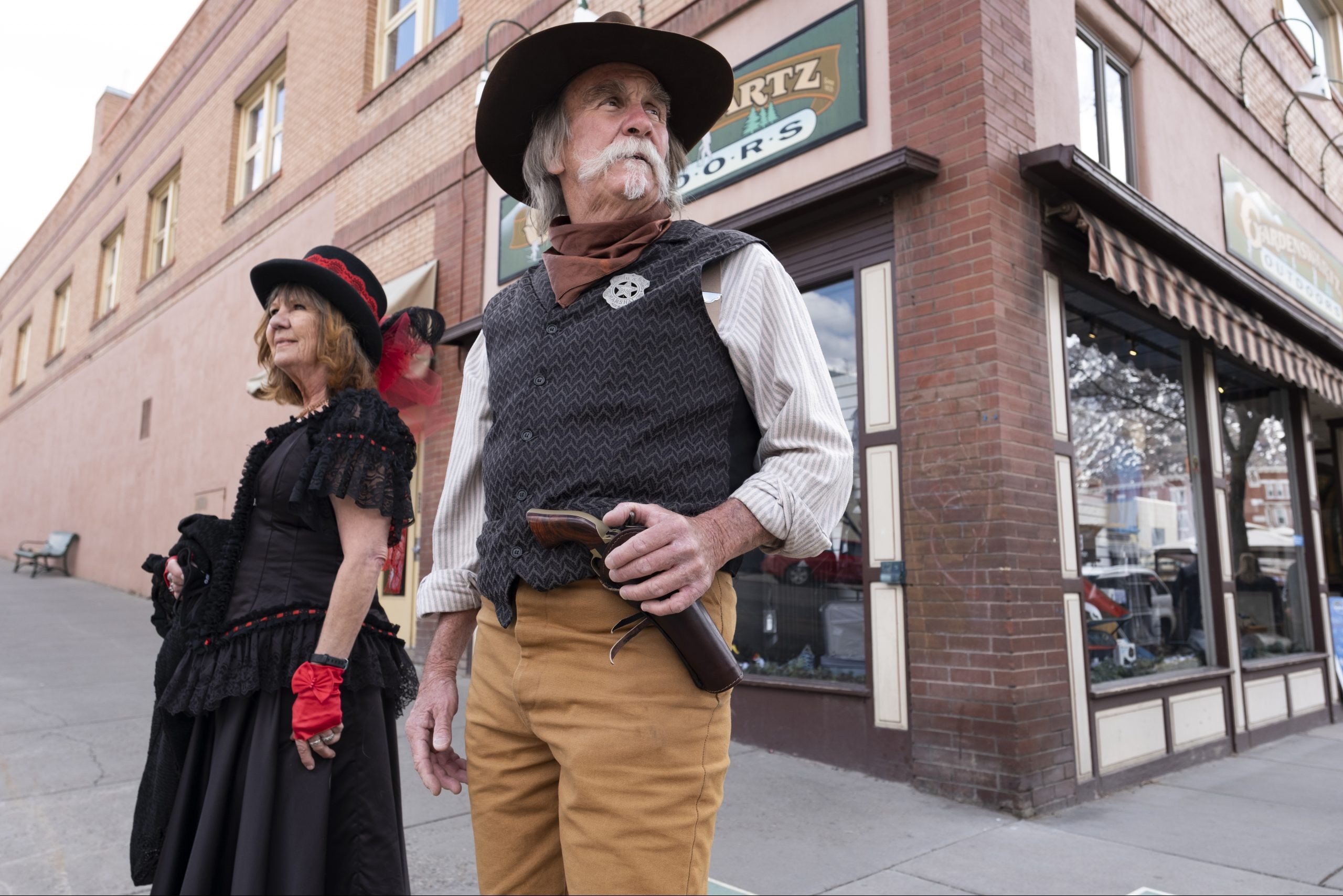 Old West actors Cathy Roberts and Scott Perez stand on the lookout for unmasked visitors in Durango, Colorado, on March 21, 2021. Durango doesn't require people to wear masks outdoors but does when people enter any businesses or public buildings. (Jeremy Wade Shockley for KHN)
