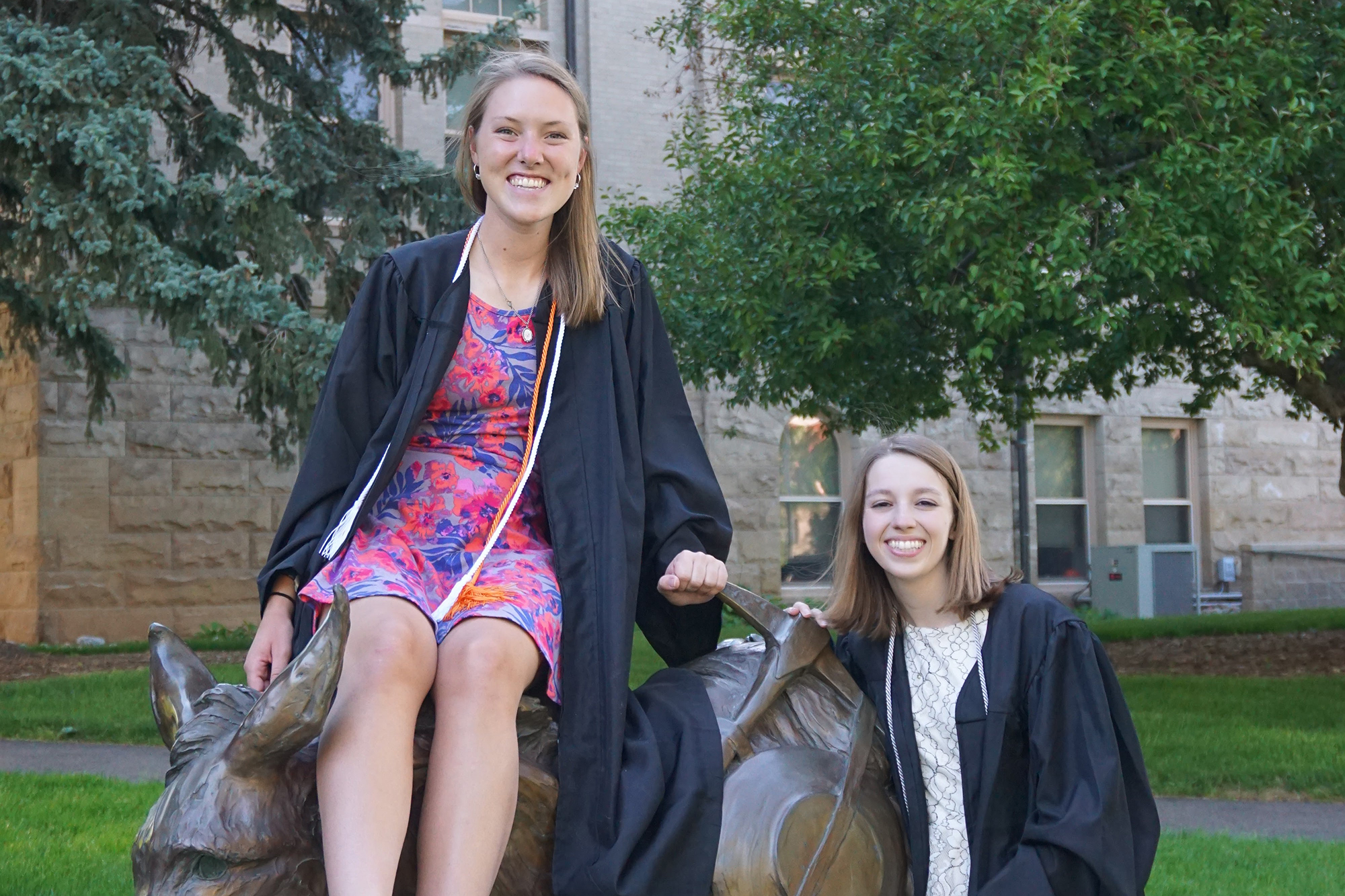 Claire Teklitz, left, and Elise Madonna pose in their graduation gowns with the Colorado School of Mines's bronze burros statue.