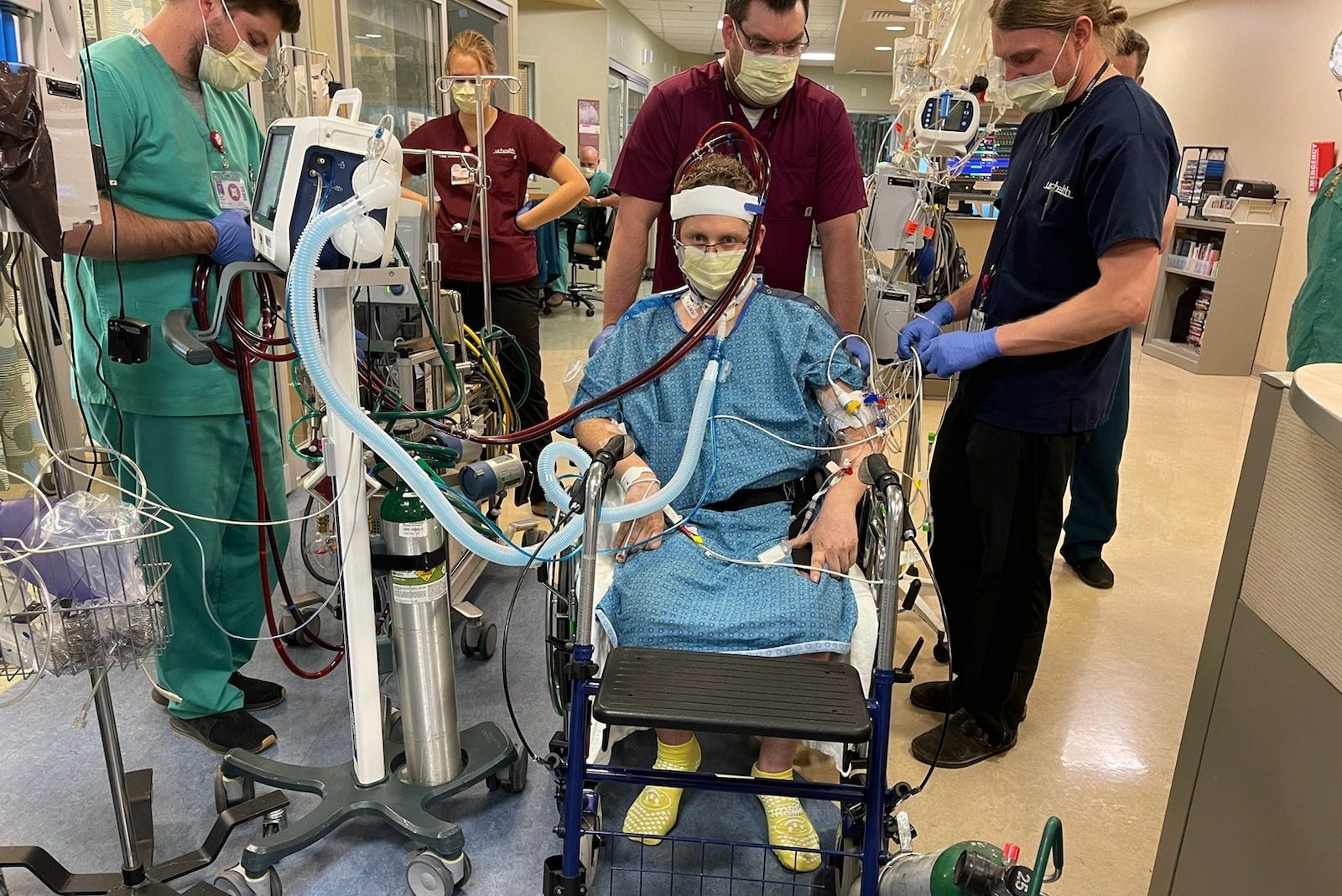 A team of medical workers surrounds Bryan Raymond at UCHealth University of Colorado Hospital.