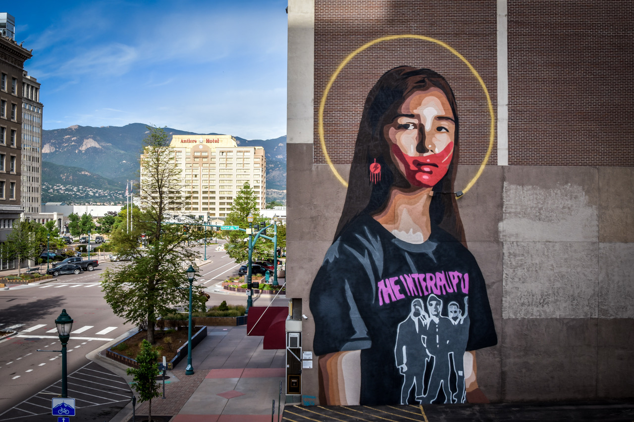 """Gregg Deal, Pyramid Lake Paiute artist and activist, painted the mural, """"Take Back The Power,"""" that overlooks downtown Colorado Springs in 2020. Deal painted the red handprint to call attention to the high rates of violence against Indigenous women, girls and LGBTQ people."""