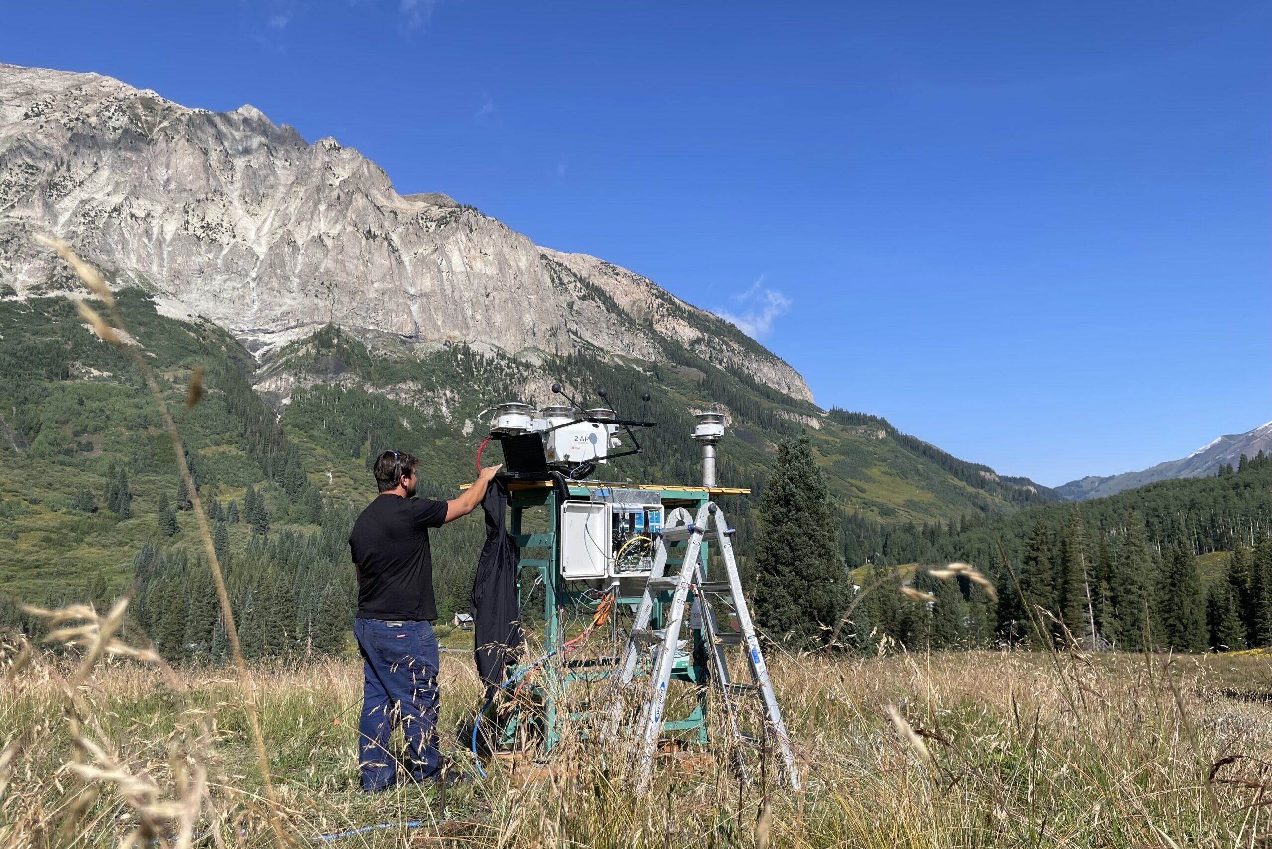 A field technician works with research equipment for the SAIL campaign in Gothic, Colo. on August 20, 2021.