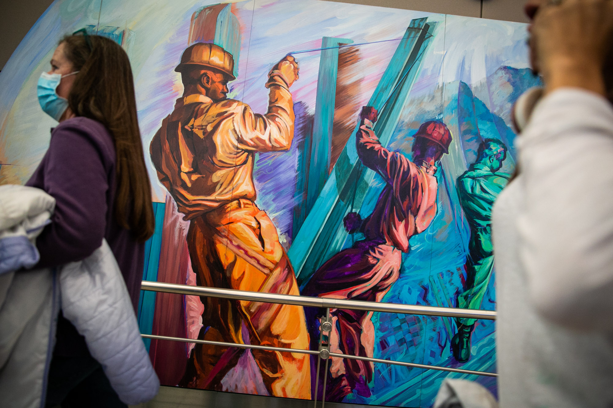 """Passengers walk by part of the """"Mile High and Rising"""" mural by Marcus Akinlana in the Jeppesen Terminal at Denver International Airport"""