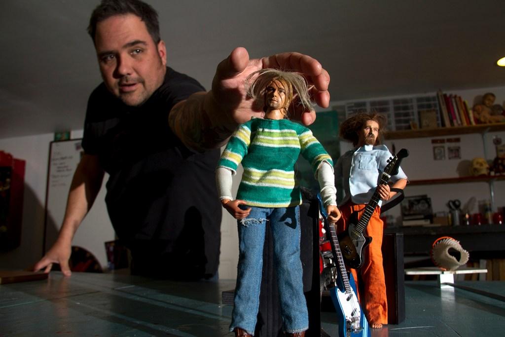 John Johnston reaches to adjust a miniature Kurt Cobain. (Kevin J. Beaty/Denverite)  denver; denverite; colorado; art; nirvana; kurt cobain