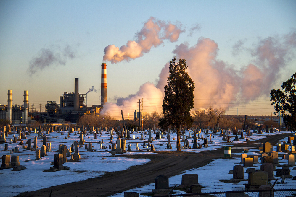 Vapor spilling out of the Cherokee Generating Station at dawn colors the sky beyond Riverside Cemetery. (Kevin J. Beaty/Denverite)