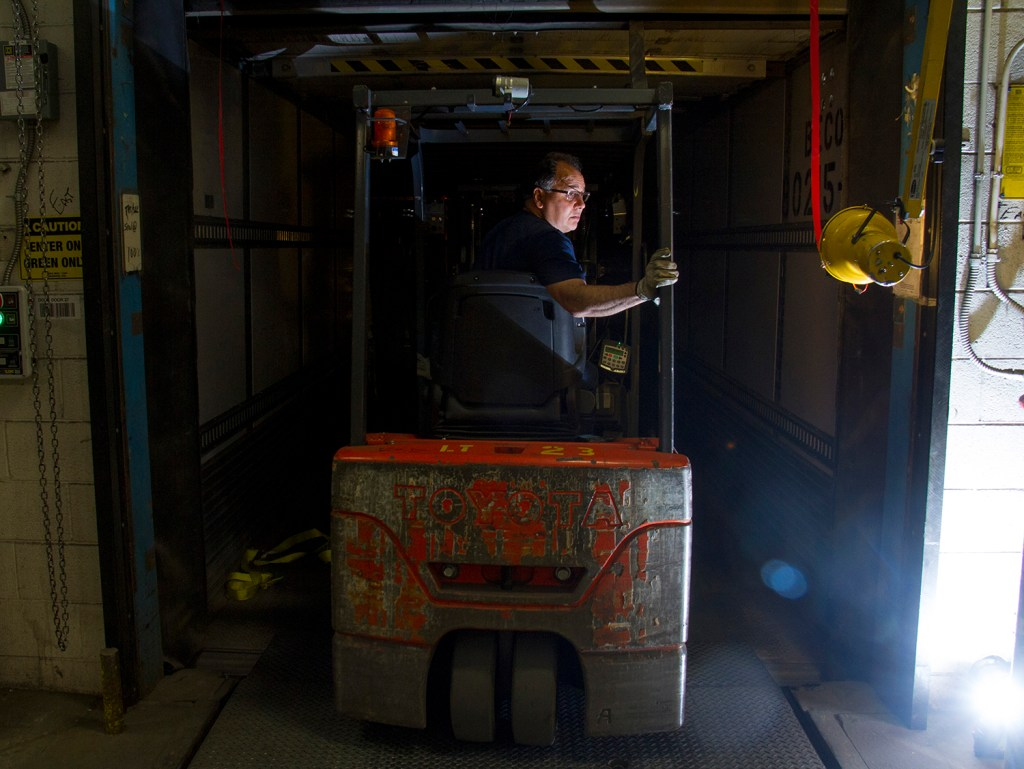 Mitch Martinez maneuvers a forklift, placing sorted units of parcels into a truck headed to the next facility in the next stop closer to delivery. (Kevin J. Beaty/Denverite)