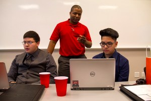 QEP IT Sharepoint Admin Chich Gillespie instructs rising high school juniors Bladimir Fernandez Jr. (left) and Juan Flores how to operate the company's network to communicate and save work. (Kevin J. Beaty/Denverite)