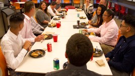 A table of interns and mentors eat together during an internship orientation for students placed at Denver-based QEP Resources Inc through Denver Public Schools' CareerConnect program. (Kevin J. Beaty/Denverite)  technical education; qep; denver; denverite; colorado; kevinjbeaty; job training; career skills; internship; denver public schools; dps;