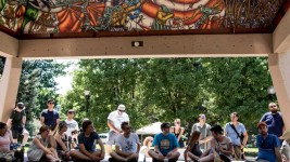 Stompin' Ground Games attendees sit beneath a mural by David Ocelotl Garcia at Columbus Park/La Raza. (Chloe Aiello/Denverite)