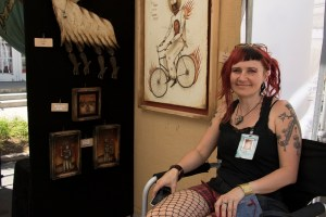 "Ellie Rusinova sits with her ""Dancing Bones"" exhibit. It is her fifth year at the festival. (Chloe Aiello/Denverite)"