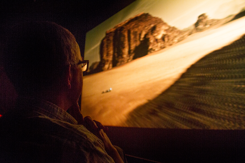 "Dr. Steven Lee watches ""The Martian"" during a Denver Film Society event at the Denver Museum of Nature and Science. Lee is Department Chair & Curator of Planetary Science at the museum and his work focuses on the interaction of surface and atmosphere on Mars. Needless to say he was the keynote presenter after the film, discussing the planet's weather and geography differ from the on-screen depiction. (Kevin J. Beaty/Denverite)  denver museum of nature and science; dmns; denver film society; dfs; movie; science; mars; denver; kevinjbeaty; colorado; denverite"