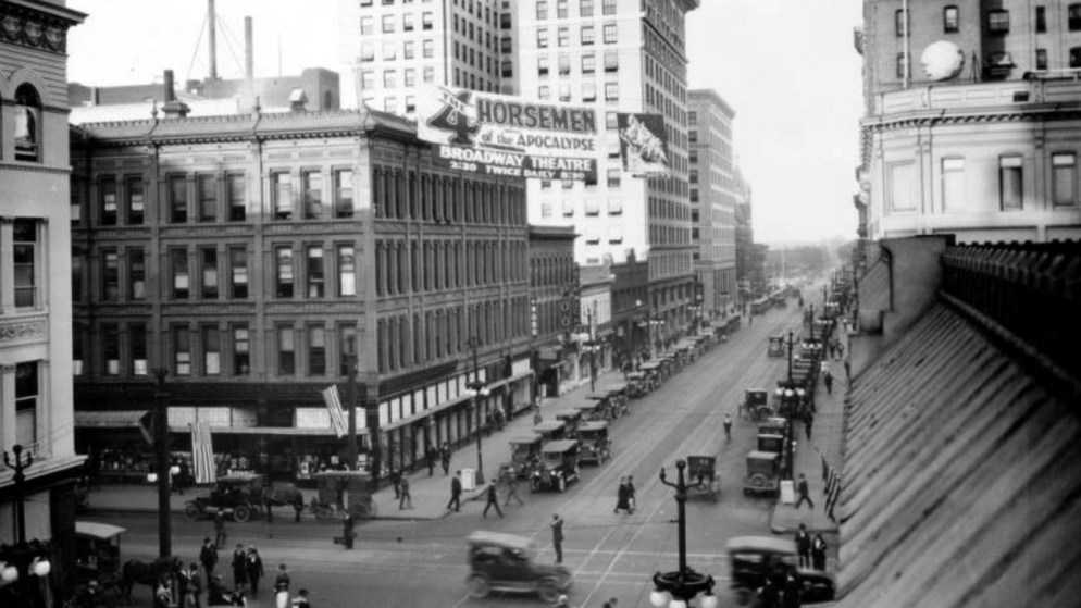 """View of 16th (Sixteenth) Street at Stout Street in downtown Denver, Colorado. Pedestrians, automobiles, and a horse-drawn carriage are in the street. Buildings include the Barth Building. Signs read: """"Kendrick Bellamy"""" """"The Ross"""" """"Pool"""" Pickwick Cafe"""" and """"The 4 Horsemen of the Apocalypse Broadway Theatre."""" Between 1910 and 1920. (Rocky Mountain Photo Company/Denver Public Library/Western History Collection/X-23054)"""