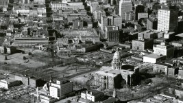 """Aerial view of the Colorado State Capitol building, a park, 15th (Fifteenth) and 16th (Sixteenth) Streets, Broadway and Lincoln Street in the Central Business District of Denver. Colorado. Shows the Denver City and County Building annex, the Carnegie library building, the Voorhies Memorial, reflecting pool and fountains in Civic Center Park, First Presbyterian Church on Broadway, the State Medical Examiners Office, the State Museum, the Colorado State Bank, the Republic Building, the Denver Theater Building, the Conoco building and the Paramount Theater. Businesses line the streets, signs read: """"Gump"""" """"Walgreen Drugs"""" and """"Used Cars."""" Bill boards and standing signs read: """"Country Club Beer, Famous For Its Flavor"""" """"Phillips 66 Runs Smoother"""" and """"Burlington Route Zephyr."""" The excavation site for the Hilton Hotel is on Court Place. (John A. Myers/Denver Public Library/Western History Collection/(Denver Public Library/Western History Collection/Z-11640)  cityscape; capitol hill; civic center; historic; denver public library; dpl; archive; archival; denverite"""