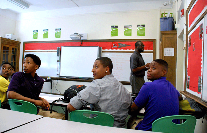 Freshmen at DSST Cole High School in Dexter Korto's morning advisory class look to the back of the class where English standards are posted. Korto, standing, taught at DSST Cole Middle School before following the freshman to open the new high school in northeast Denver.  (Photo by Nicholas Garcia)