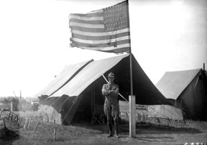 A soldier, in uniform, poses outside a staked walled tent beside a flag pole with a fringed American flag at Fort Logan, Colorado. World War I. 1917. (George L. Beam/Denver Public Library/Western History Collection/GB-7581)  denver public library; dpl; archive; archival; world war I; military; george l beam; denverite;